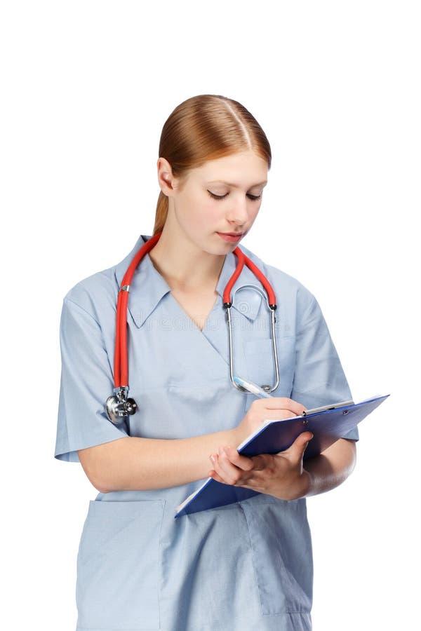 Mujer joven en capa quirúrgica azul con el estetoscopio y el papel rojos imagen de archivo