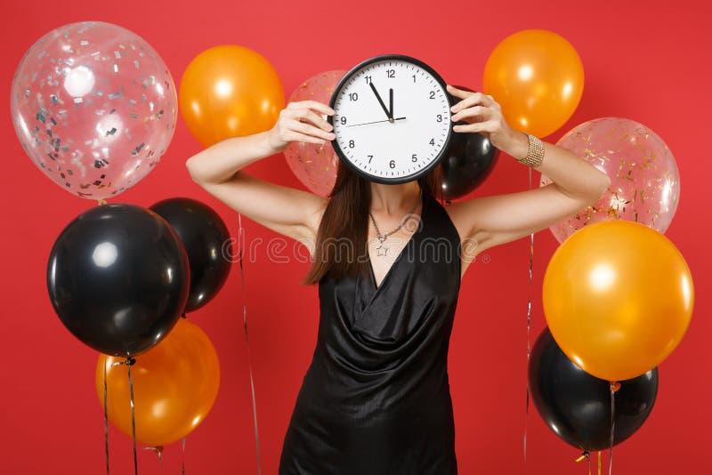 Mujer joven en cara negra de la cubierta del vestido con el reloj redondo en los balones de aire rojos brillantes del fondo El ti fotografía de archivo libre de regalías