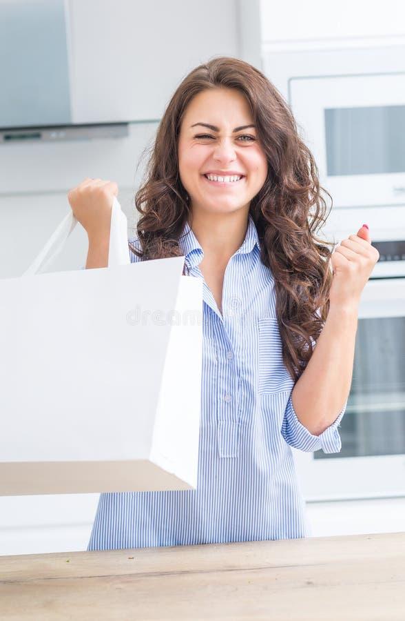 Mujer joven en casa en la cocina con un bolso que hace compras que disfruta de una buena compra imágenes de archivo libres de regalías