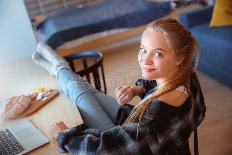 Mujer joven en casa en la cocina que come y que usa el ordenador portátil fotos de archivo