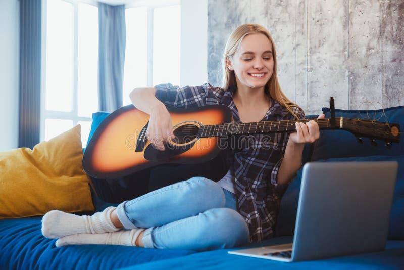 Mujer joven en casa en las lecciones del vídeo de la afición de la sala de estar imágenes de archivo libres de regalías