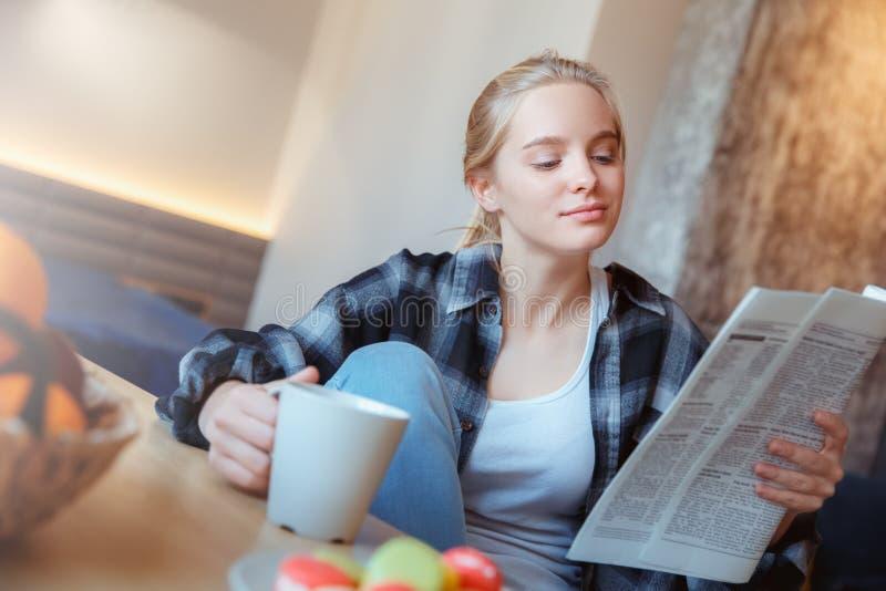 Mujer joven en casa en las noticias de consumición de la lectura del té de la cocina imagenes de archivo