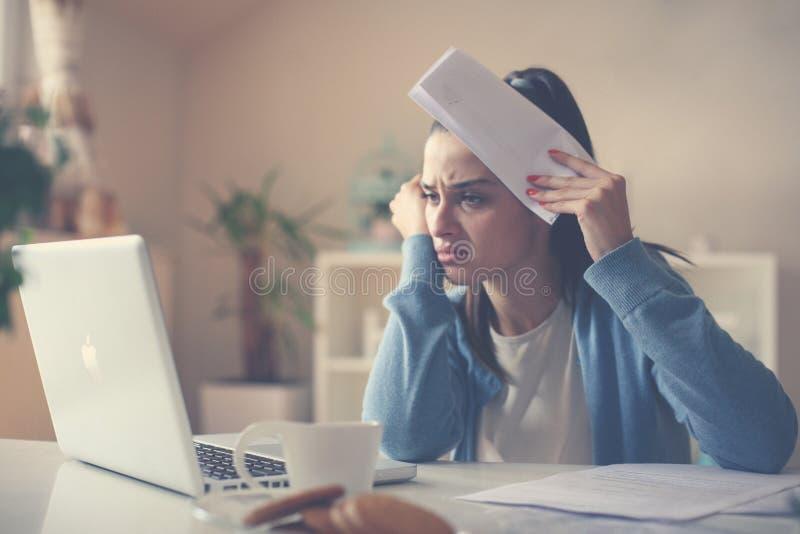 Mujer joven en casa usando el ordenador portátil y cuentas el sostenerse fotos de archivo libres de regalías