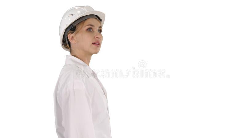 Mujer joven en casco que da une vuelta y que mira en el fondo blanco foto de archivo