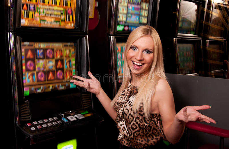 Mujer joven en casino en una máquina tragaperras fotos de archivo libres de regalías