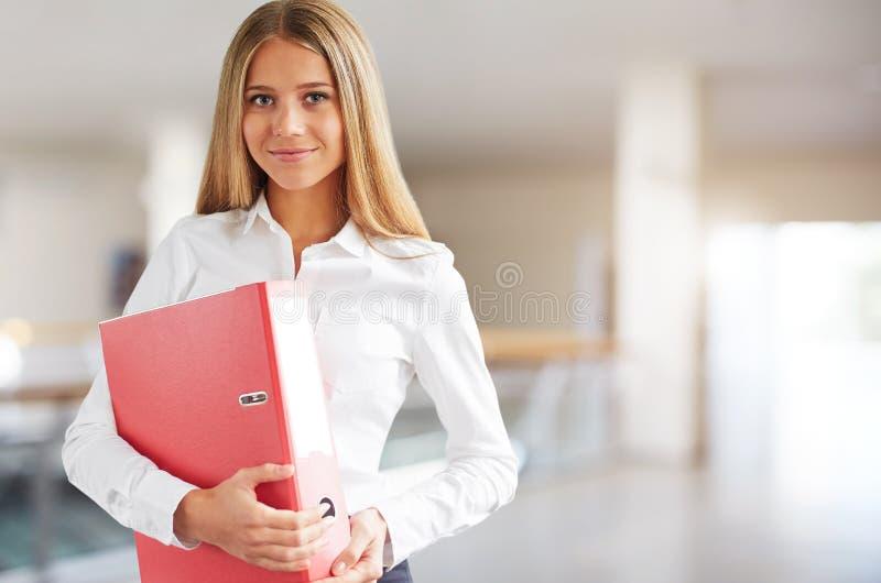 Mujer joven en centro de negocios con la carpeta en manos imagen de archivo libre de regalías