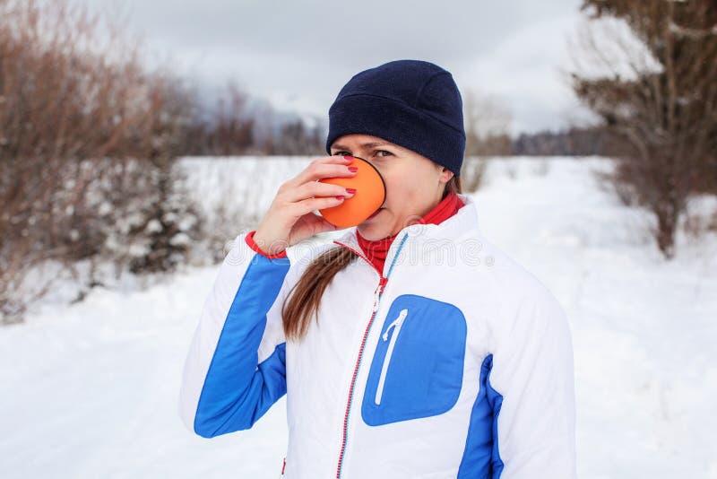 Mujer joven en chaqueta de deporte de invierno que bebe té caliente fotos de archivo