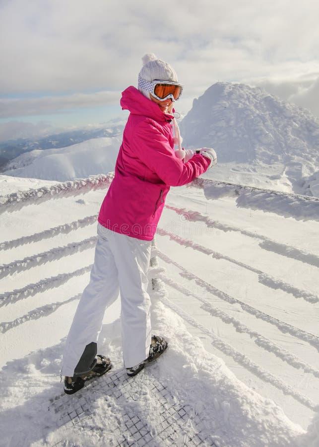 Mujer joven en chaqueta de esquí, botas de los pantalones, sombrero y guantes rosados, inclinándose en el carril nevado, mirando  imagen de archivo libre de regalías