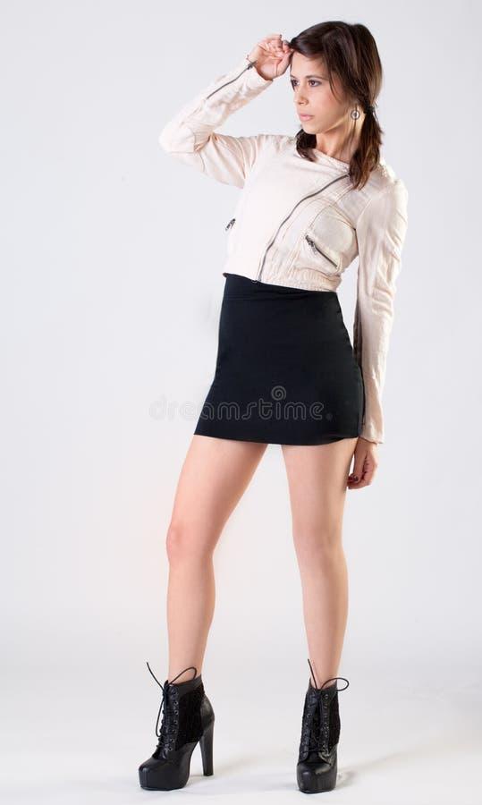 Mujer joven en chaqueta, falda, y botas imagenes de archivo