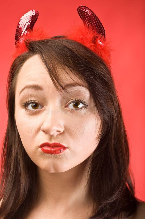 Mujer joven en claxones de los diablos foto de archivo