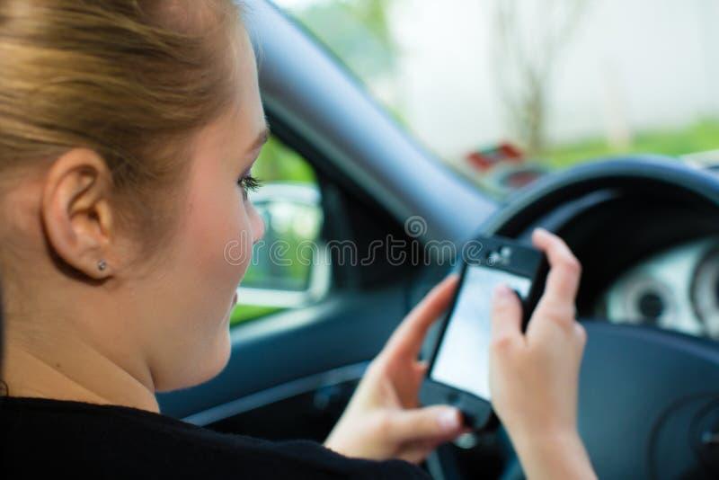 Mujer joven, en coche con el teléfono móvil imagen de archivo