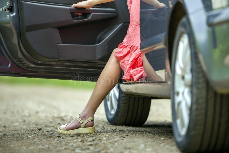 Mujer joven en coche que sale del vestido corto con la puerta abierta en fondo rural borroso soleado del camino fotos de archivo
