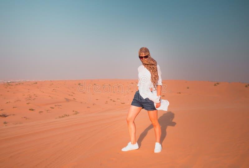 Mujer joven en desierto Turista en el desierto de Dubai en fondo claro del cielo foto de archivo libre de regalías