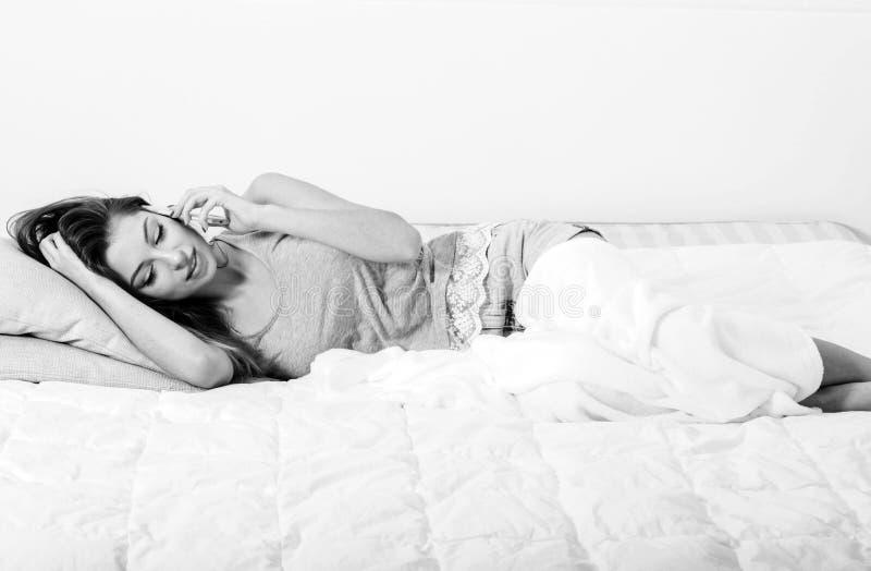 Mujer joven en dormitorio con el teléfono móvil en el dormitorio blanco y negro imagen de archivo