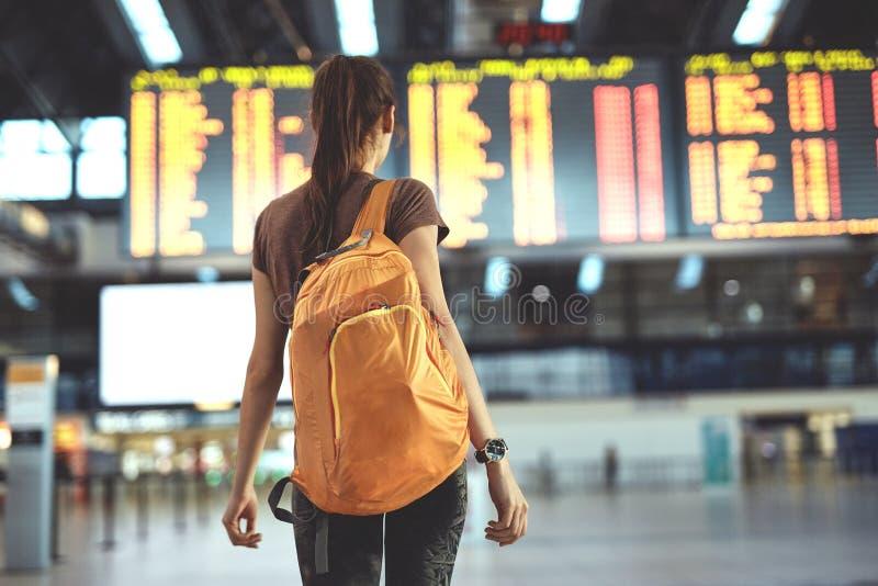 Mujer joven en el aeropuerto internacional que mira al tablero de la información del vuelo fotos de archivo