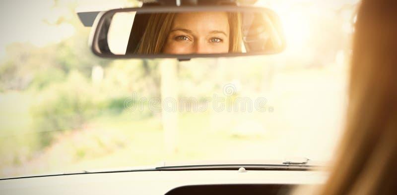 Mujer joven en el asiento de conductores que mira en el espejo fotografía de archivo libre de regalías