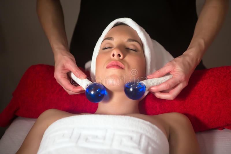 Mujer joven en el balneario que tiene masaje de cara imagenes de archivo