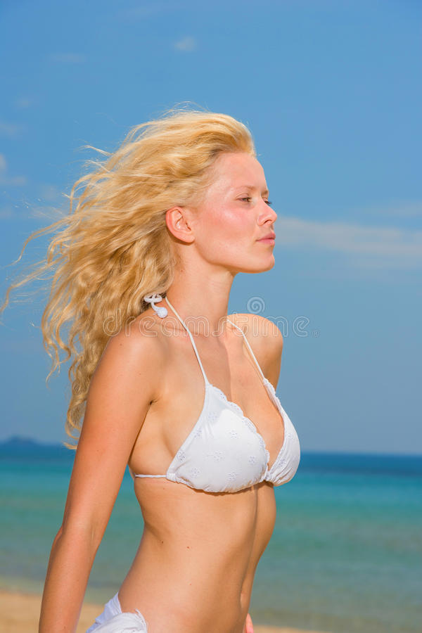 Mujer joven en el bikini blanco que sostiene los sarong en la playa fotos de archivo