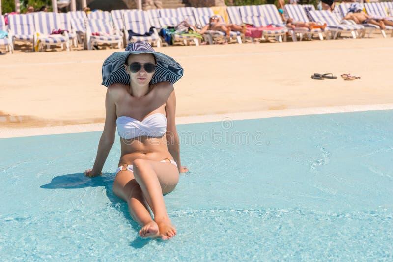 Mujer joven en el bikini que se relaja en la piscina del centro turístico imagenes de archivo