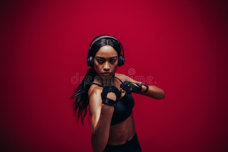 Mujer joven en el boxeo de la ropa de deportes en fondo rojo fotos de archivo
