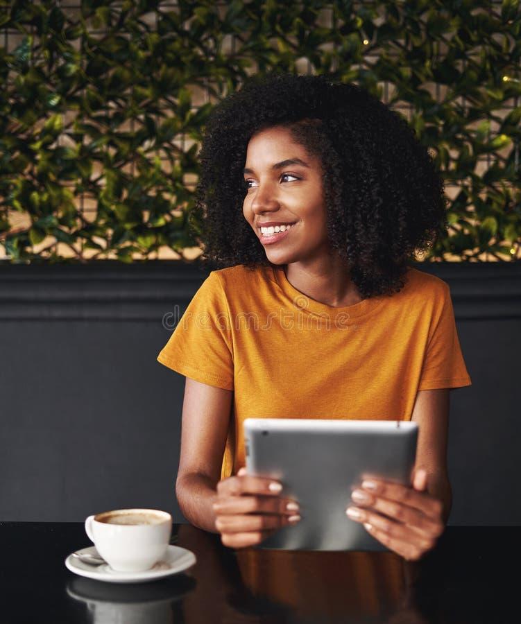 Mujer joven en el café que sostiene la tableta digital que mira lejos foto de archivo libre de regalías