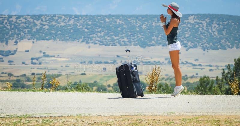 Mujer joven en el camino con equipaje imagenes de archivo