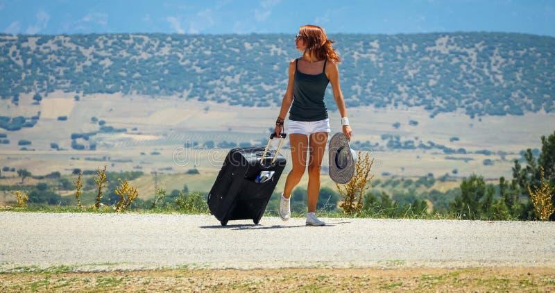 Mujer joven en el camino con equipaje imagen de archivo libre de regalías
