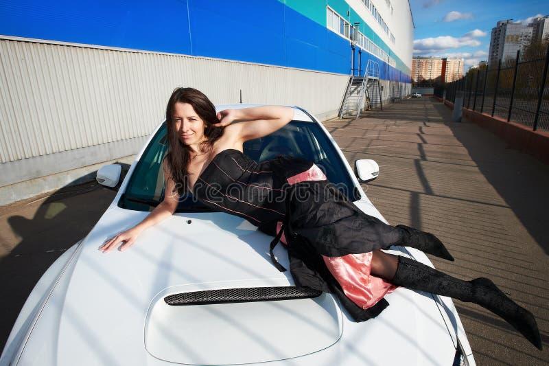 Mujer joven en el capo motor de un coche de deportes del blanco imagen de archivo libre de regalías