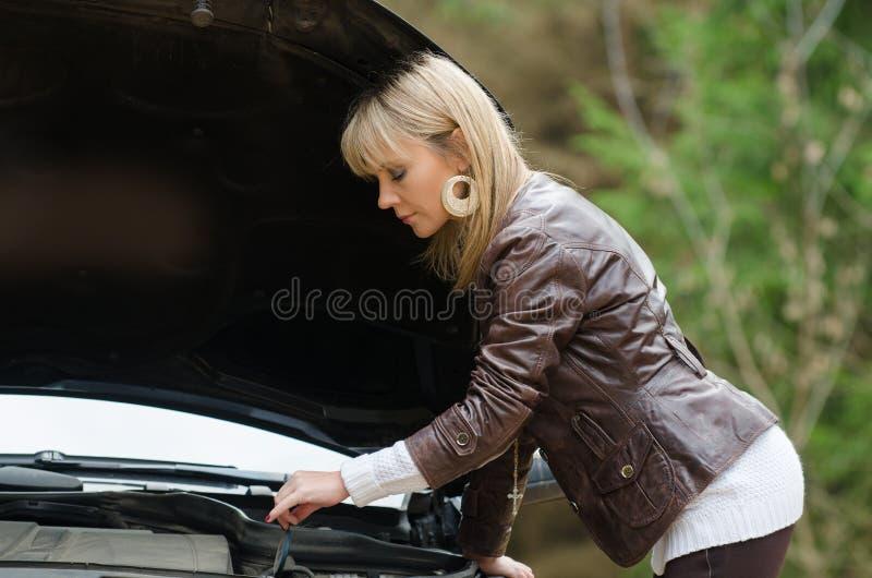 Mujer joven en el coche quebrado fotos de archivo
