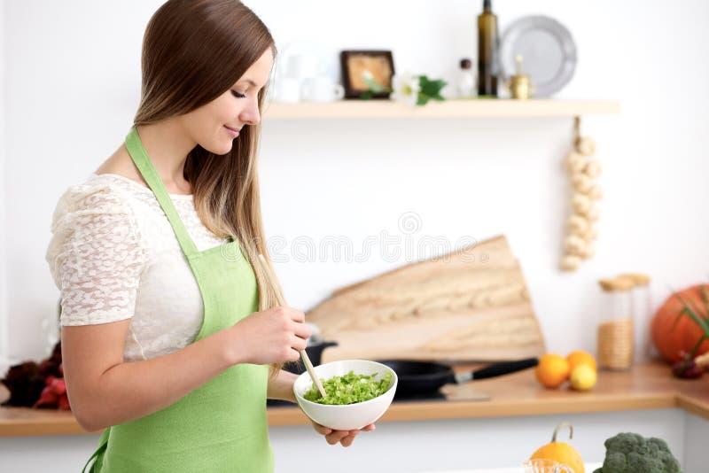 Mujer joven en el delantal verde que cocina en la cocina Ama de casa que mezcla la ensalada fresca imagenes de archivo