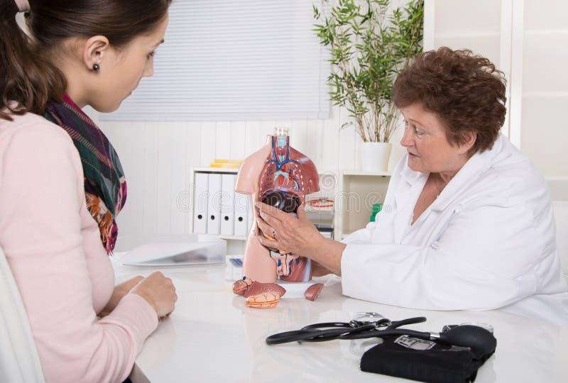 Mujer joven en el doctor - explicación del cuerpo humano foto de archivo libre de regalías