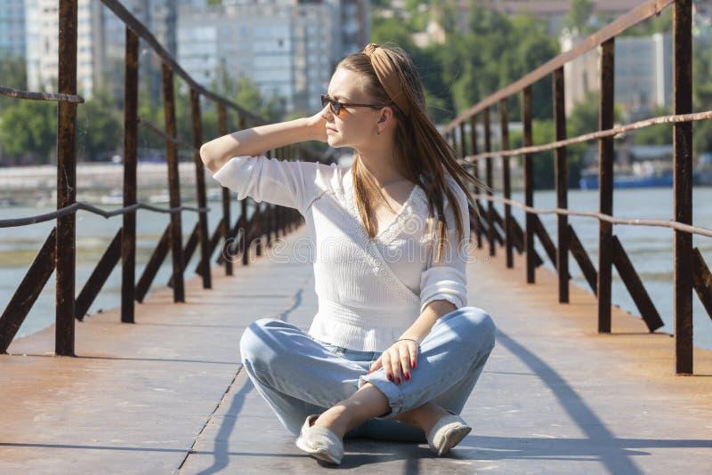 Mujer joven en el embarcadero en el río imagen de archivo