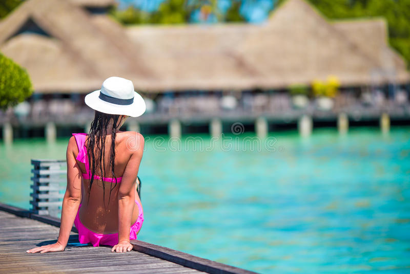 Mujer joven en el embarcadero tropical de la playa en Maldivas foto de archivo libre de regalías