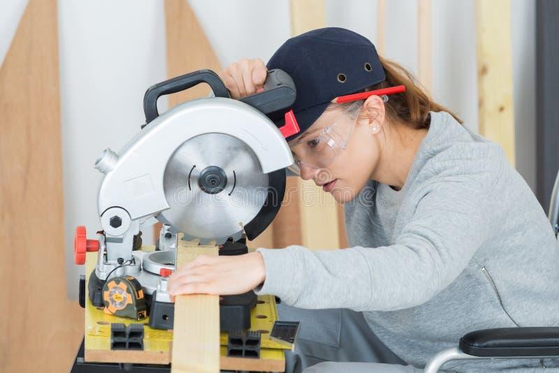 Mujer joven en el entrenamiento profesional de la carpintería fotos de archivo