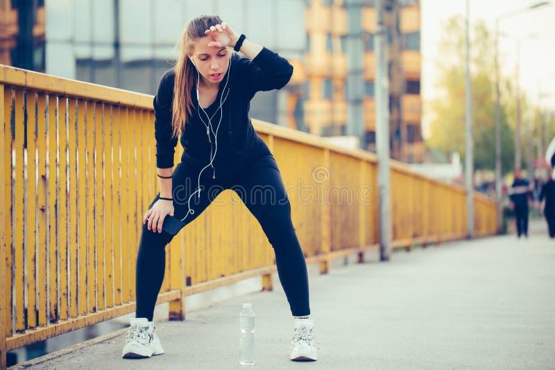 Mujer joven en el equipo negro de los deportes que descansa después de correr en el puente foto de archivo libre de regalías