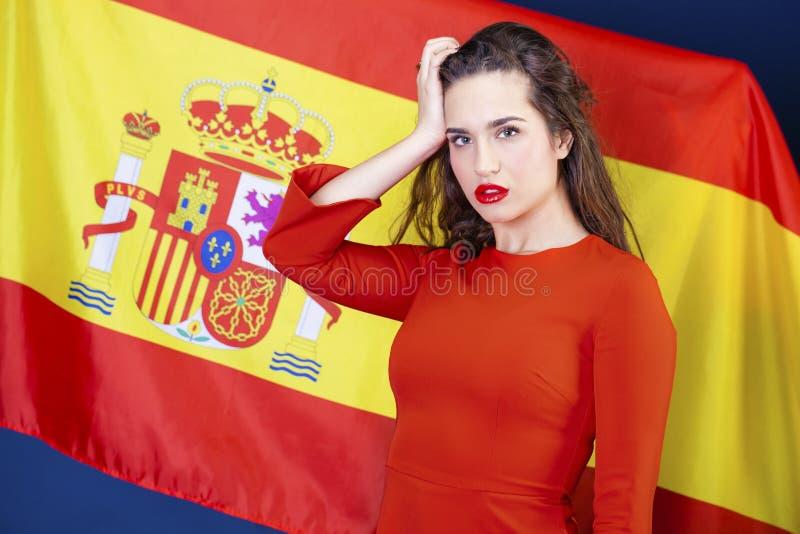 Mujer joven en el fondo de la bandera española imagenes de archivo