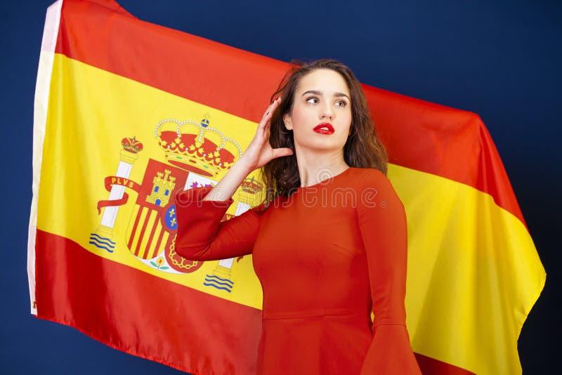 Mujer joven en el fondo de la bandera española foto de archivo