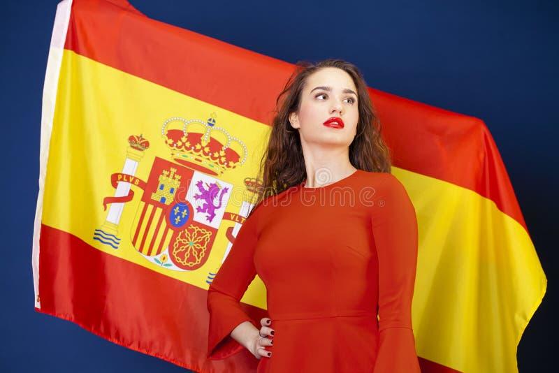 Mujer joven en el fondo de la bandera española imagen de archivo