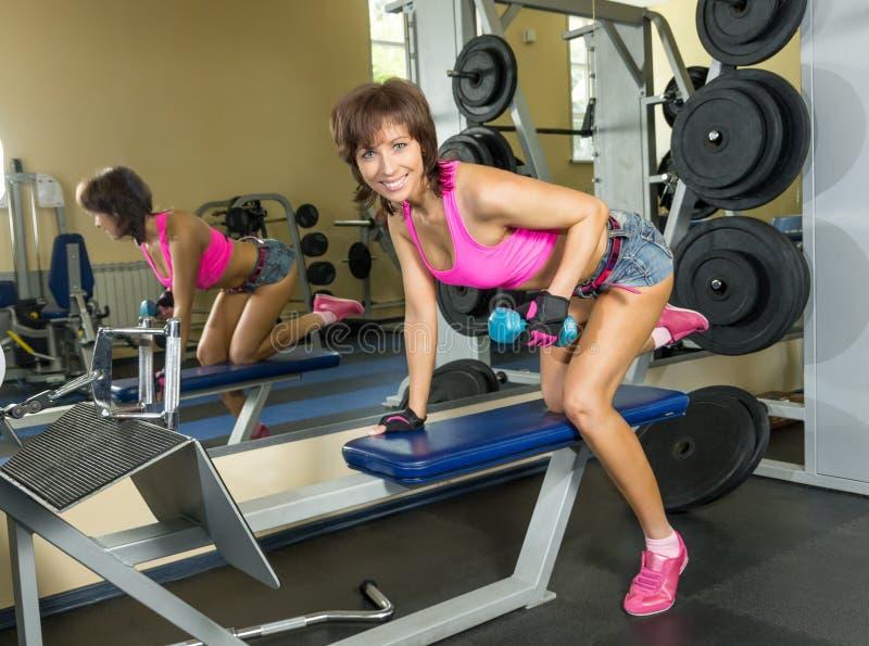 Mujer joven en el gimnasio con pesas de gimnasia imagenes de archivo