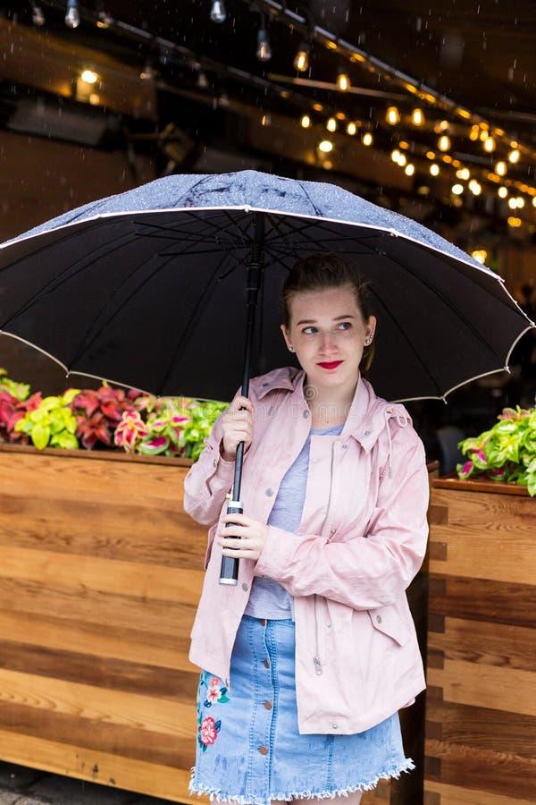 Mujer joven en el impermeable rosado abierto que se coloca que espera pacientemente debajo de un paraguas imagen de archivo