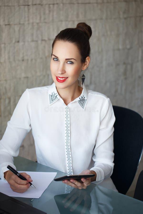 Mujer joven en el lugar de trabajo usando una tableta digital fotos de archivo