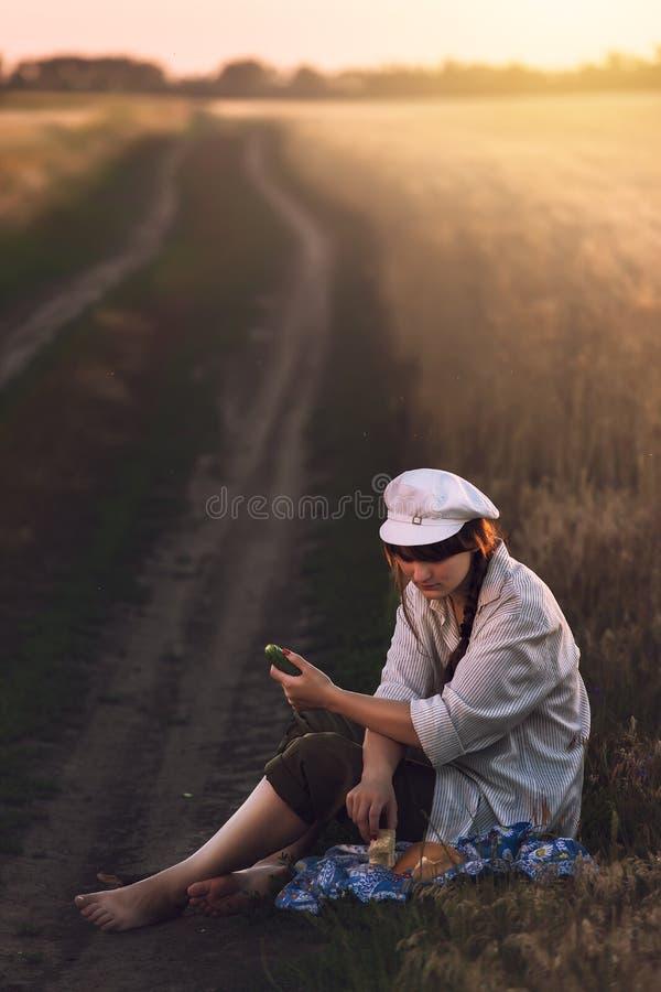 Mujer joven en el man& blanco x27; la camisa y el casquillo de s se sienta en un campo de trigo cerca del camino en la tierra y a fotografía de archivo
