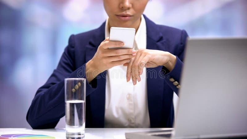 Mujer joven en el mensaje del smartphone del traje que mecanografía, uso social de las redes fotos de archivo libres de regalías