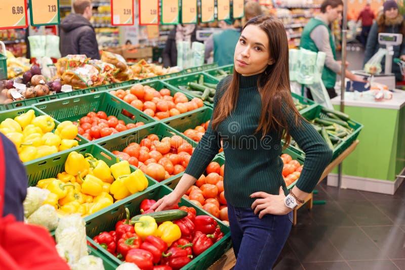 Mujer joven en el mercado con las verduras imagen de archivo