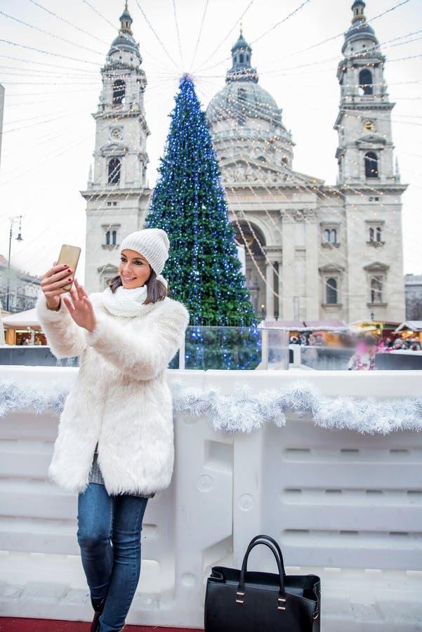 Mujer joven en el mercado de la Navidad foto de archivo