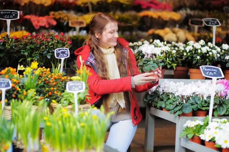Mujer joven en el mercado parisiense de las flores fotografía de archivo libre de regalías