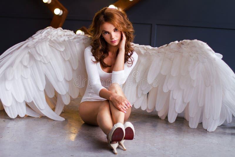Mujer joven en el mono blanco con las alas del ángel foto de archivo