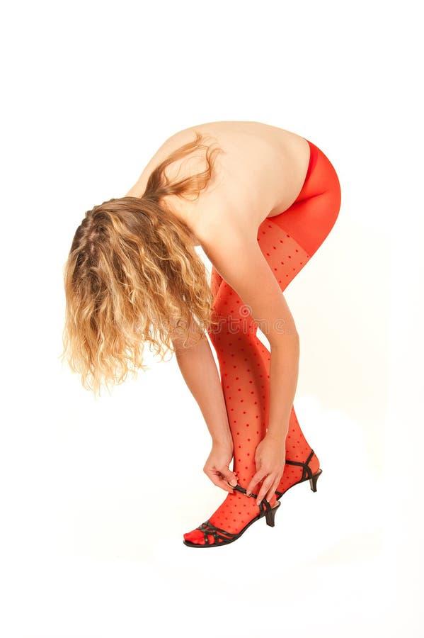 Mujer joven en el pantyhose rojo que dobla abajo imagenes de archivo