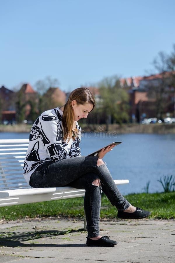 Mujer joven en el parque con una tableta fotografía de archivo libre de regalías