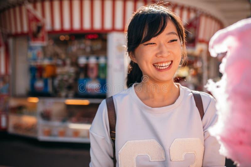 Mujer joven en el parque de atracciones con seda del caramelo imágenes de archivo libres de regalías
